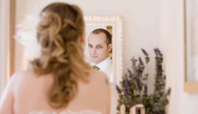 Novia maquillandose en un espejo donde se ve el reflejo del novio.